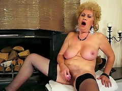 Busty grandma Effie shoves a recent sex-toy in her shaved slit in front of the fireplace