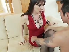 Hawt and breasty dark haired milf in sexy red costume RayVeness gets her bald taco licked on the ottoman in her living room by a lascivious juvenile dark haired dude Joey Brass and enjoys