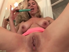 Aged plays with her tits and twat in bathroom